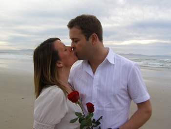Andy Rebecca Kiss By Pacific Ocean and Exchange Red Roses for Renewal of Vows Ceremony with Marilyn Verschuure from Marry Me Marilyn at Wategos Beach Byron Bay NSW Australia
